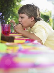 young boy (10-12) eating cupcake at birthday party