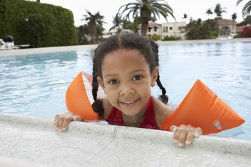 girl (5-6 years) holding on to edge of swimming pool