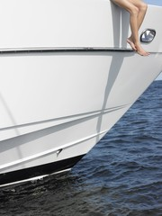 Young woman sitting at edge of yacht with legs dangling overboard, low section