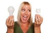 Woman Holds Energy Saving and Regular Light Bulbs poster
