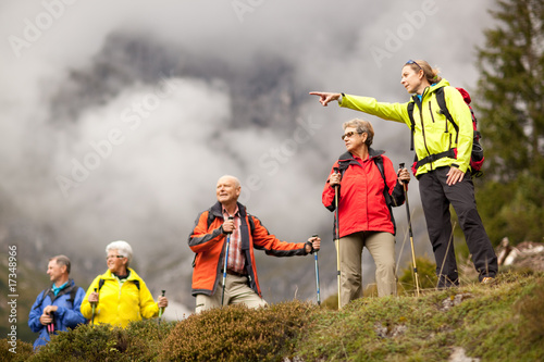 young female hiking guide showing senior group surrounding mount - 17348966