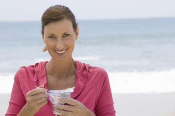 Woman eating yoghurt on beach