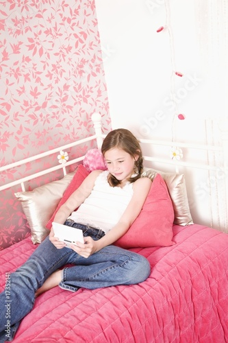 Young girl in bedroom playing handheld game