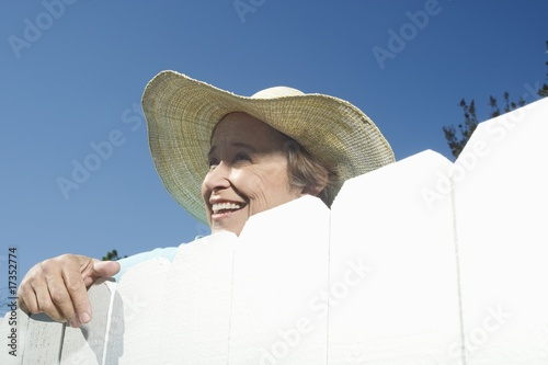 Woman peering over garden fence