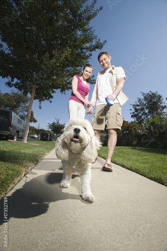 Couple walking dog along pavement