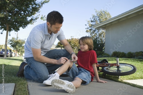 Father looking after son, bicycle laying on floor