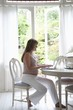 Pregnant woman sitting at table using laptop