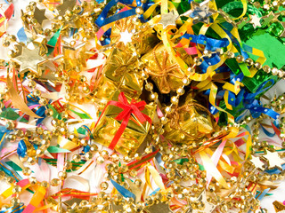 Small golden gifts around colored confetti. Shallow DOF.