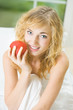 Happy young woman with apple at home