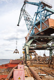 Industrial grabber the crane loads the barge scrap metal