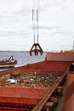 Industrial grabber loads the barge scrap metal