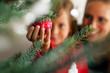 Leinwanddruck Bild - Familie schmückt Weihnachtsbaum