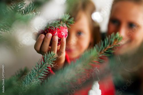 Leinwanddruck Bild Familie schmückt Weihnachtsbaum