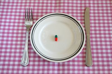 Capsules on a plate with a knife and fork, signifying dieting.