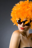pretty woman wearing an orange feather wig and sunglasses poster