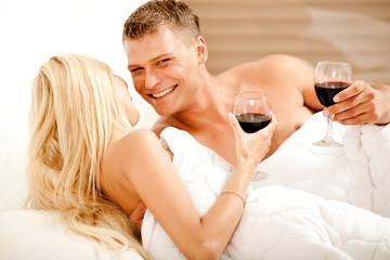 Couple enjoying wine in bed