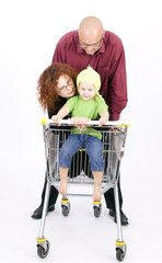 father thrusting shop trolley with mother and daughter