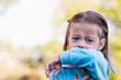Leinwanddruck Bild - Little girl coughing or sneezing into her elbow.