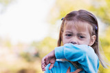 Little girl coughing or sneezing into her elbow. poster