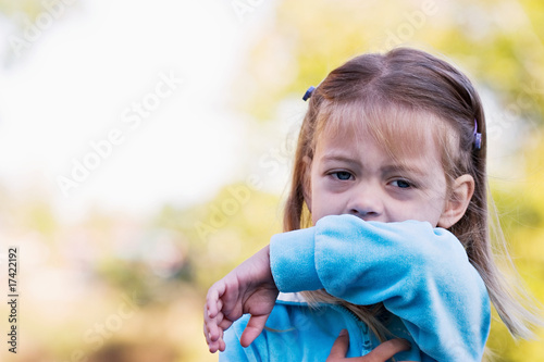 Little girl coughing or sneezing into her elbow.