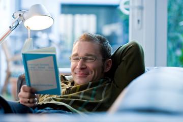 Mann entspannt sich und liest Buch