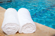Two rolled-up white towels by blue pool - 17437193
