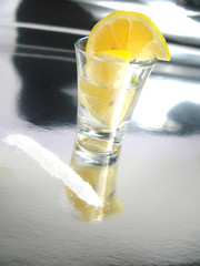 Tequila shot with lemon and salt on silver floor
