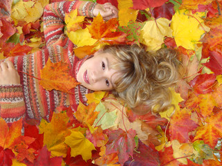 The girl lies on maple leaves.