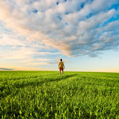 man on green field under sunset skies
