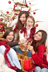 Four young woman toasting with champagne on Christmas