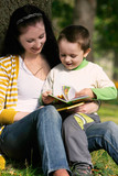 mother and son reading book in autumn park