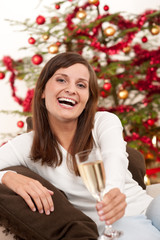 Brown hair woman sitting with glass of champagne on Christmas