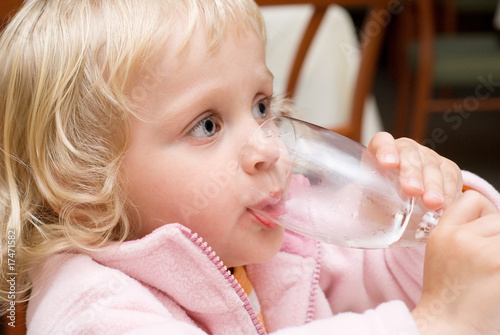 Little girl drinking water in a restaurant