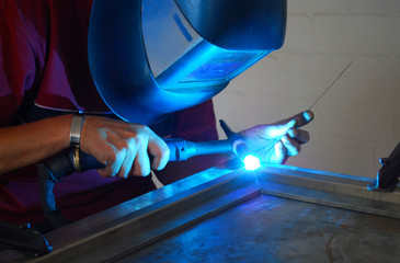 welder welding a piece of steel with blue light