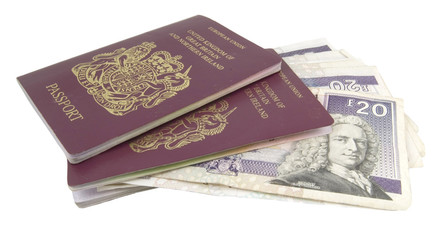 cash and two british passports on white background