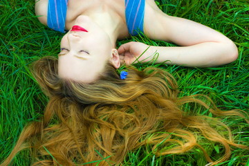 beautiful young woman with a blond hair on grass