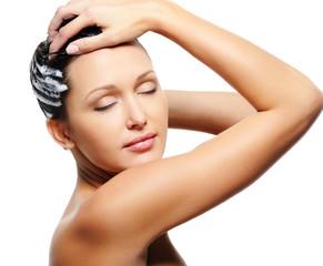woman washing her head with shampoo