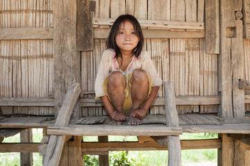 Asiatisches Mädchen Akha vor Holzhaus