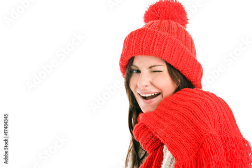 Young woman wearing red scarf and cap winking