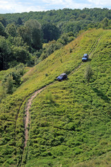 Off-road. Two 4x4 jeeps tries to climb up top of a hill