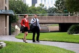 Coworkers engaged in conversation walking in urban park.