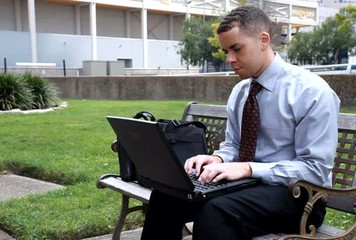 Businessman wireless laptop outside downtown park