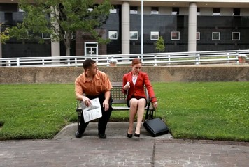 On park bench man woman look at want ads