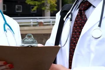 Doctor nurse outdoors discuss chart