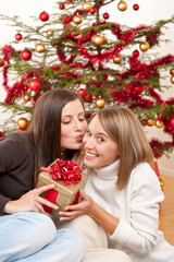 Two smiling women with Christmas present kissing