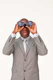 Surprised Afro-American businessman looking through binoculars