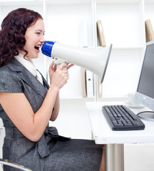 Businesswoman yelling through a megaphone