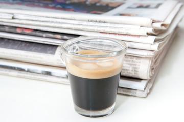 Espresso neben Zeitungen