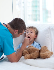Male doctor examining child throat