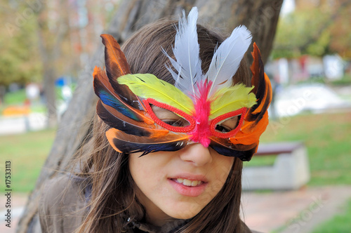 A young girl wearing a feather mask